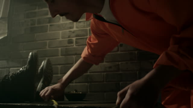 Male prisoner cleaning table in jail