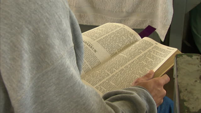 Male prisoner hands holding Bible leafing in Old Testament to first pages of Book of Habakkuk Christianity Christian sacred scriptures religion...