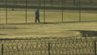 Male prisoner walking alone along interior fence of maximum security prison yard wrapped razor wire of perimeter fence FG Incarceration correctional...