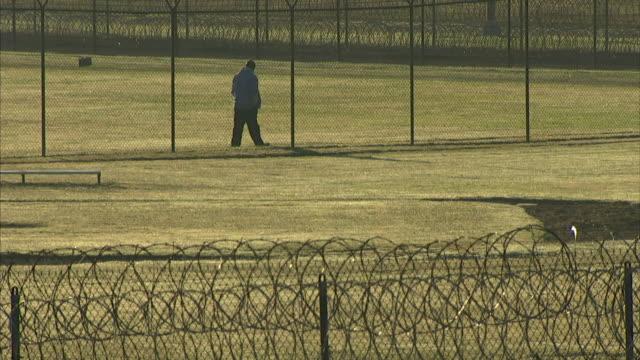 Male prisoner walking alone along interior fence of maximum security prison yard wrapped razor wire of perimeter fence FG Incarceration correctional...
