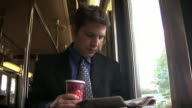 Male professional reading newspaper and drinking coffee next to window onboard commuter rail