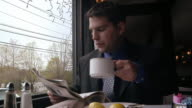 Male professional reading newspaper and taking sip of tea at table next to window in restaurant / rising from seat