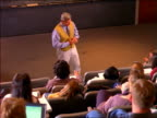 Male professor in front of lecture hall talking to seated students / Boston, MA