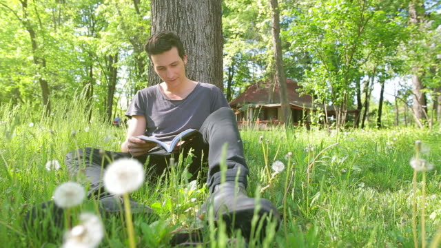 Male reading a book in park.