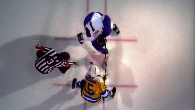 OVERHEAD male referee drops hockey puck in face off / opposing male players battle for control