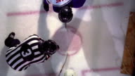 OVERHEAD MS male referee drops hockey puck in face off / opposing male players battle for control
