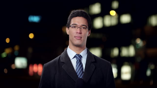 Male reporter reporting live from the city at night