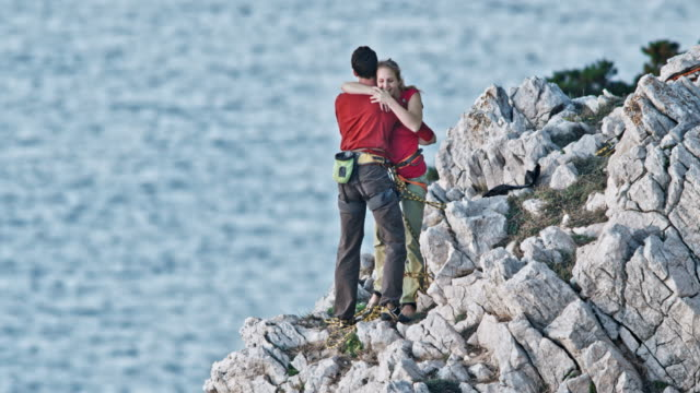 Male rock climber reaching the top of the rugged cliff and celebrating with female climbing partner