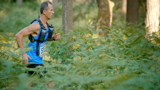 SLO MO DS Male runner running a marathon through the forest