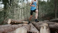 SLO MO DS Male runner running across a stock of logs in the forest