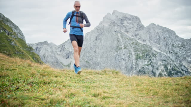 DS Male runner running down a grassy path overlooking a peak in the high mountain range