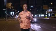 SLO MO TS mannelijke atleet lopen in de stad bij nacht