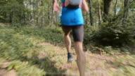 TS Male runner running through the forest