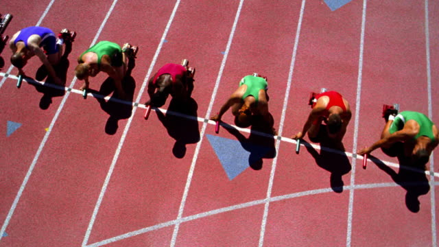 OVERHEAD male runners holding batons taking off from starting blocks on track