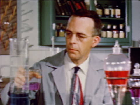1952 male scientist pouring purple liquid from beaker into container / PAN to bubbling red liquid