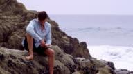 M/S Male sitting on rocks beside ocean