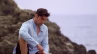 M/S Male sitting on rocks on beach