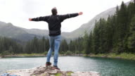 Male standing on rock with arms wide enjoying freedom