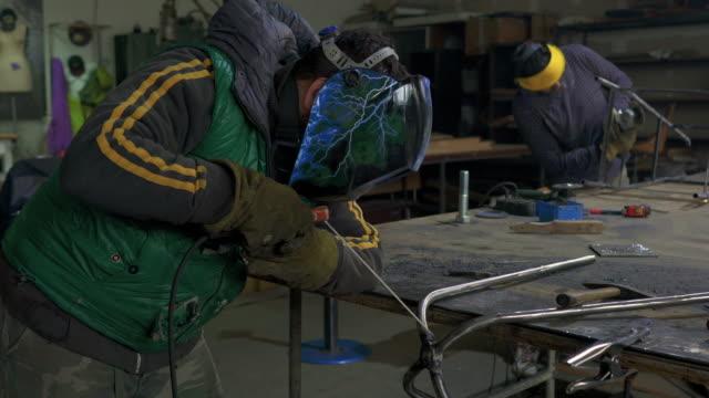 Male steel workers welding iron in a workshop.