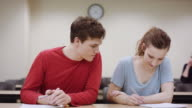 Male student comparing his work with female classmate