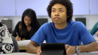 Male Student Interacts uses a Digital Tablet in Classroom