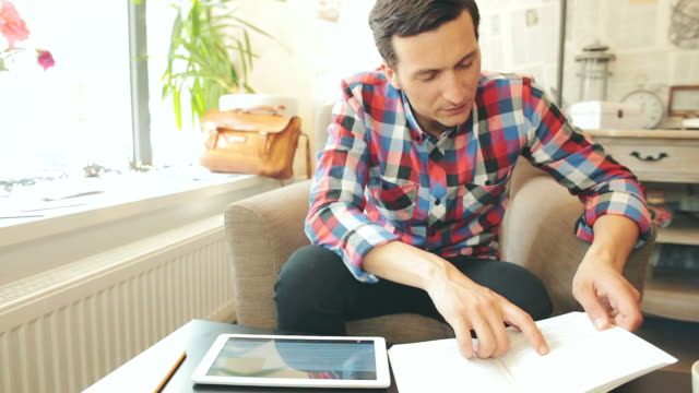 Male studying or researching using a book and a digital tablet.