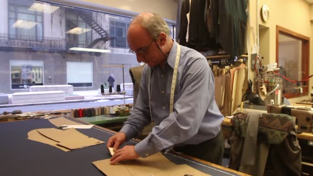 A male tailor involved in various stages of making custom suits and garments at Richard Bennett Custom Tailors in Chicago Illinois A male tailor...