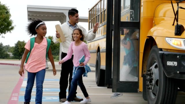 Male teacher greets diverse school children as they disembark from a school bus