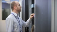 Male technician checking cable connections in the server room