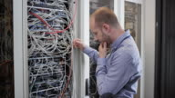 Male technician stressing over cables in server room