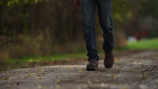 A male torso wearing blue jeans, work boots, vest and camouflage shirt walks down gravel road in autumn.