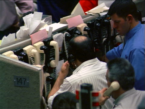 Male traders talking on telephone at bank of phones / Coffee, Sugar + Cocoa Exchange, NYC
