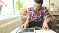 Mannelijke met behulp van een digitaal tablet en het lezen van een boek.