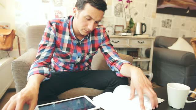 Mann mit einem Digitaltablett während beim Buchlesen.