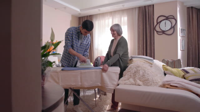 Male volunteer ironing clothes for senior lady