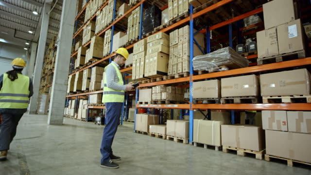 CS Male warehouse employee checking the pallet racks in a warehouse