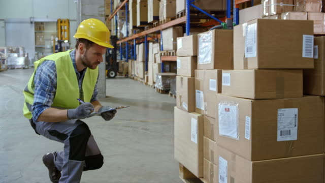 Male warehouse employee doing an inventory of the packages stacked on a pallet in the warehouse