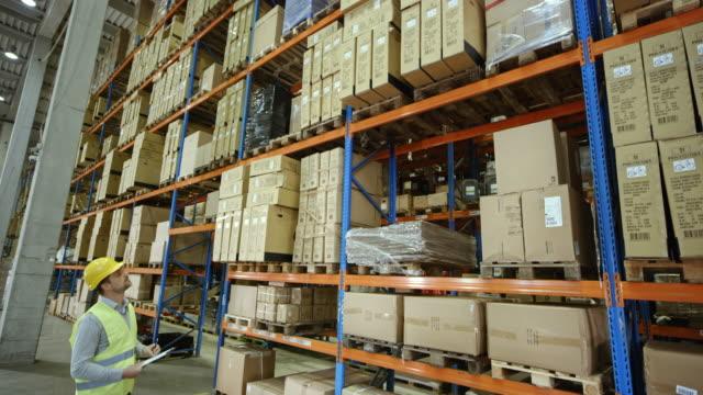 CS Male warehouse supervisor checking the pallet racks in a full warehouse