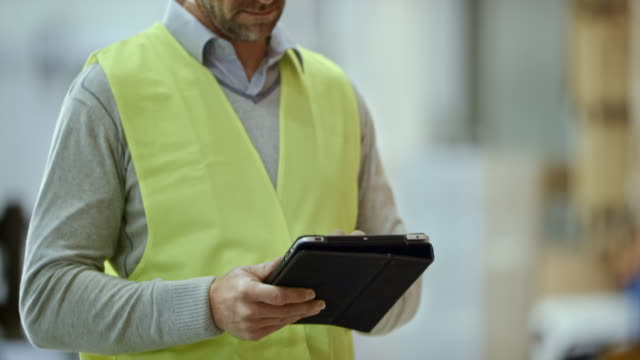 Male warehouse supervisor entering data into the tablet while checking the pallet racks