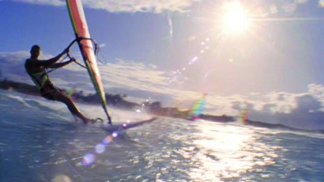 PAN male windsurfer speeding past camera on ocean / Hawaii