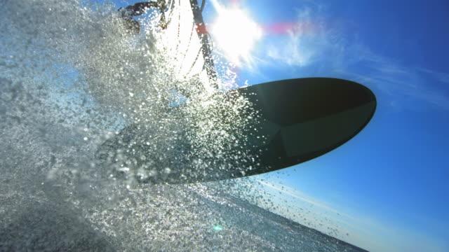 Male windsurfer splashing camera