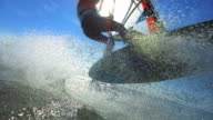 Male windsurfing jump with waterdrops, timeramp