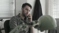 Male worker talking on phone at desk