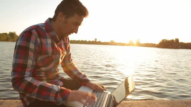 Male working at his laptop in nature at sunset.
