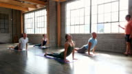 MS Male yoga instructor leading students in sun salutation sequence during yoga class