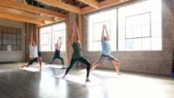 MS Male yoga instructor leading students in sun salutation sequence during class