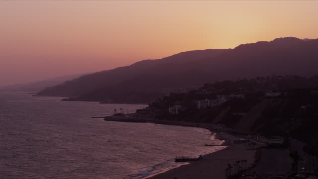 Malibu coastline, Pacific Coast Highway and rippling ocean beneath golden sky just after sunset