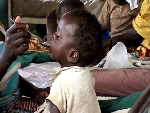 Malnourished toddler being fed in crowded hospital ward, Walungu. Democratic Republic of Congo