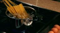 POV man adding pasta to boiling water