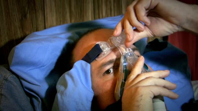 Man adjusting CPAP mask before bed